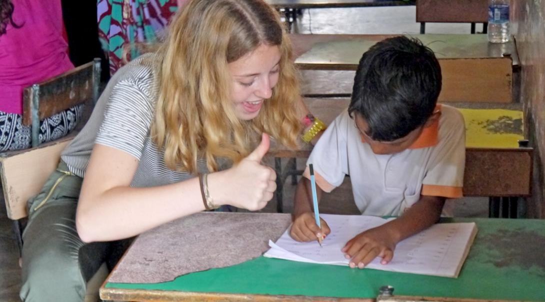 Childcare volunteer encourages a kindergarten student during class in India.